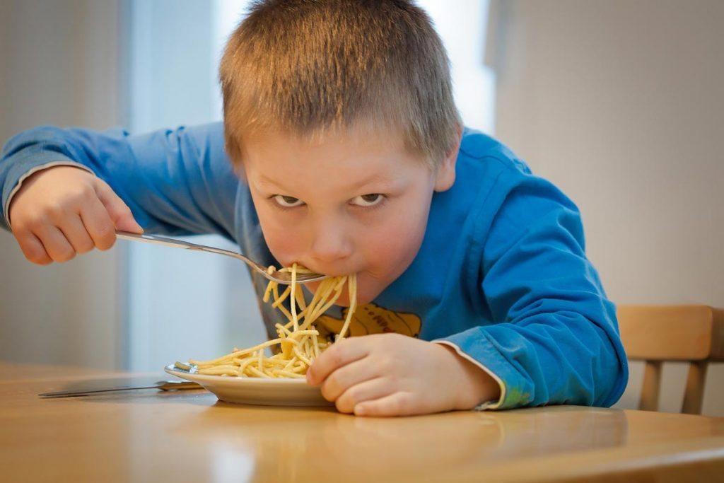 Kid eating noodles.