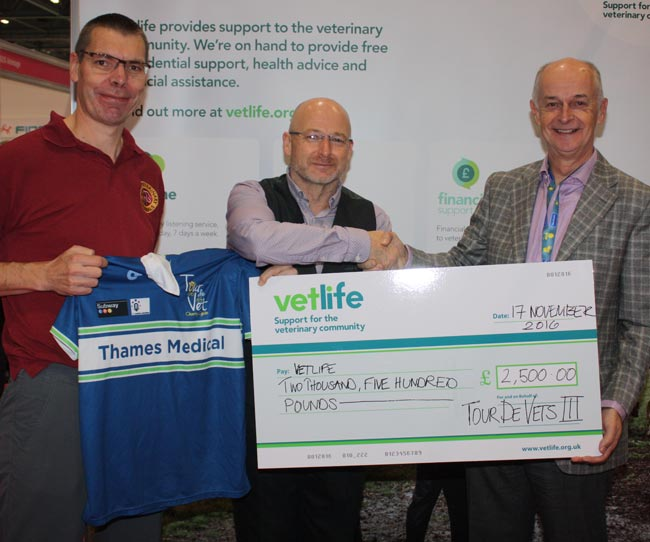 Vetlife president Geoff Little receives the results of the efforts of Tour de Vets cyclists Mike Brampton and Alasdair Hotston-Moore.