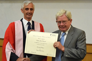 Dean of the vet school Gary England welcomes John Newcombe as honorary professor.