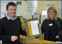 Director Pete Southerden and client care team member Claire Webster proudly holding Eastcott Vets IIP Bronze Award certificate