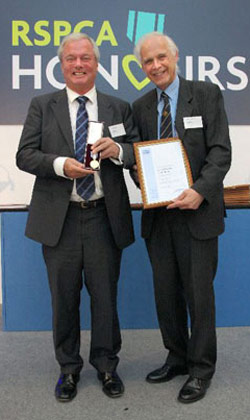 David Grant (left) receives his award from RSPCA chief executive Gavin Grant