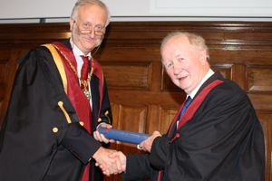 RCVS senior vice-president Peter Jinman hands Des Thompson his fellowship scroll